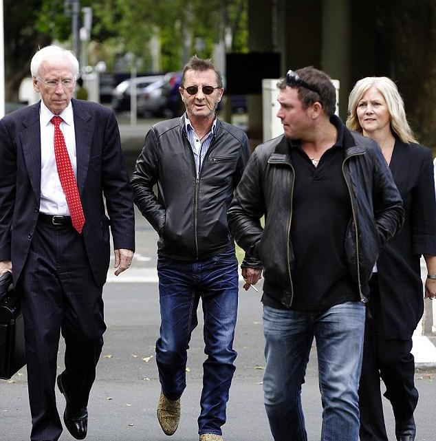 Foto de Phil Rudd e seus advogados mais cedo nesse ano.