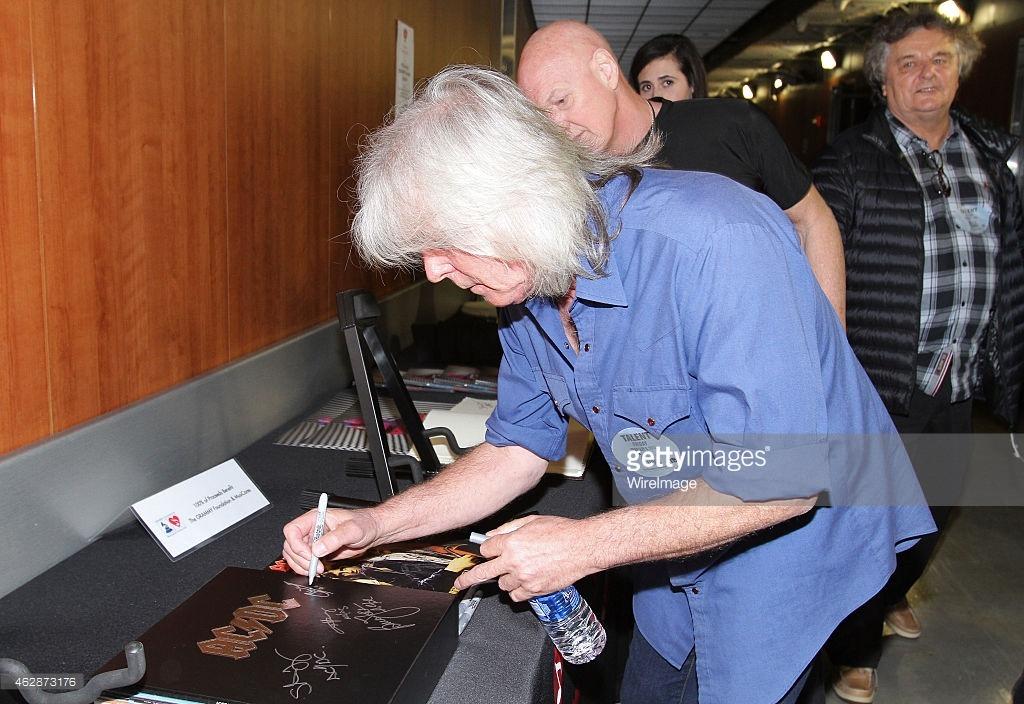 Cliff Williams e Chris Slade assinando itens da discografia do AC/DC que serão utilizados para caridade. 6 de feverairo de 2015, Los Angeles, California, EUA. (Foto por Maury Phillips/WireImage)