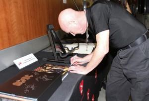 Chris Slade assinando alguns itens da banda para o leilão de caridade do Grammy (07/02/2015)